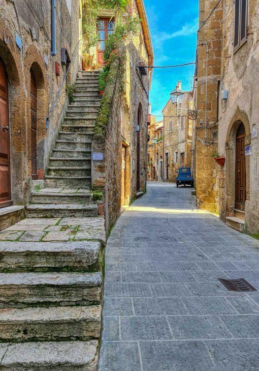 Plakat z wąską uliczką w toskańskim miasteczku